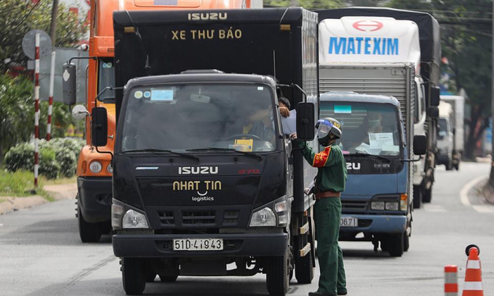 Військовий офіцер перевіряє проїзні документи вантажівки на блокпості Covid-19 у Хошиміні. Фото VnExpress/Quynh Tran